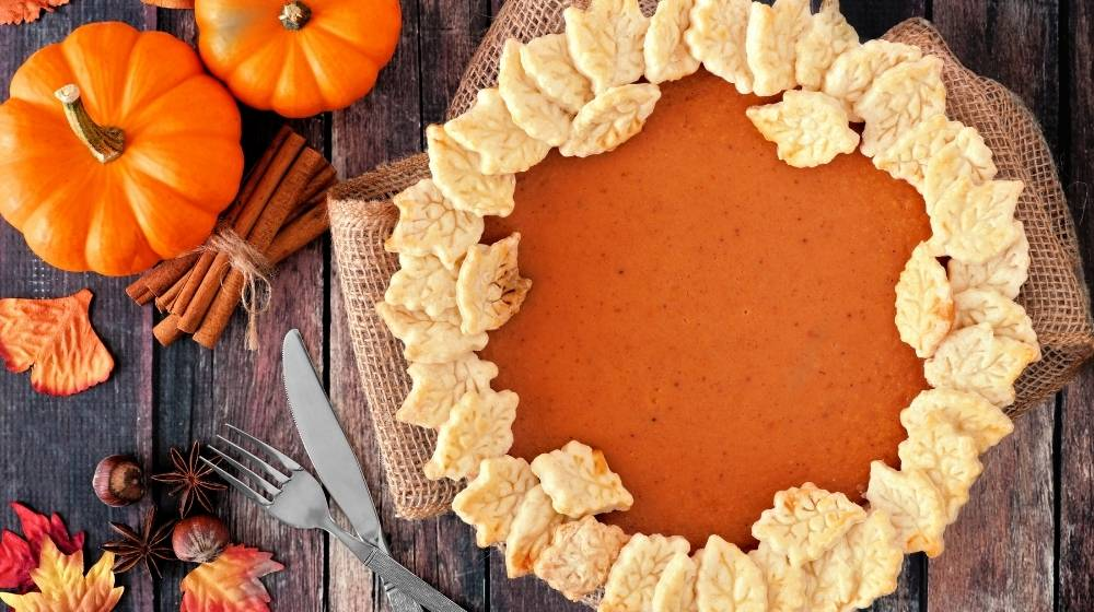 Pumpkin Pie decorated with pastry leaves on a wooden board   Feature   The Best Vegan Pumpkin Pie Recipe