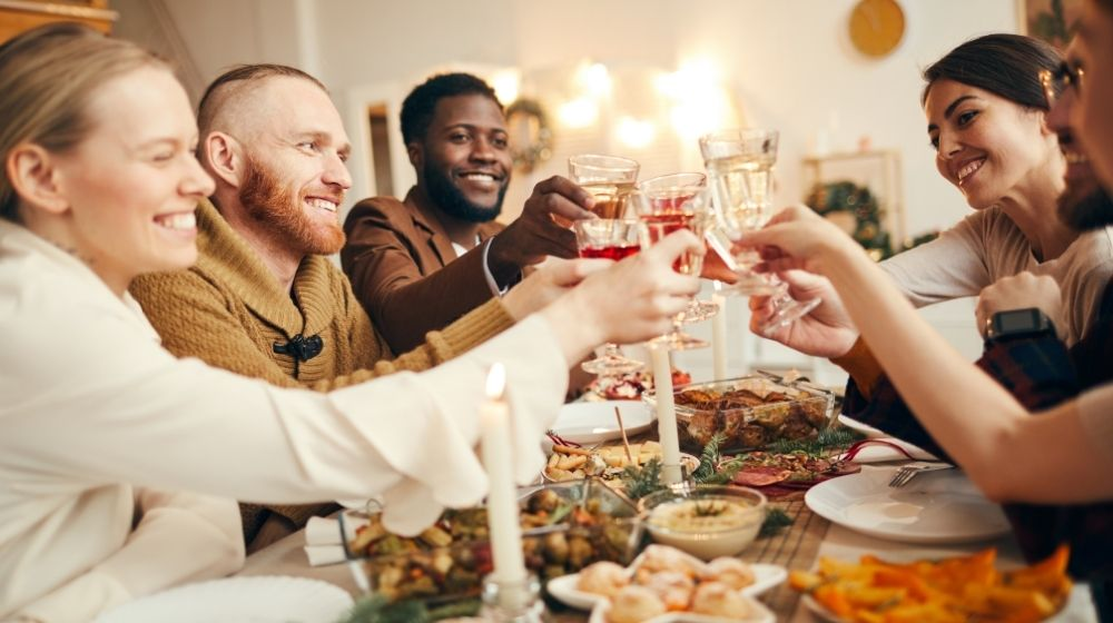 group of people raising glasses sitting at beautiful dinner table celebrating Thanksgiving | Feature | Vegan Thanksgiving Dishes For The Whole Family