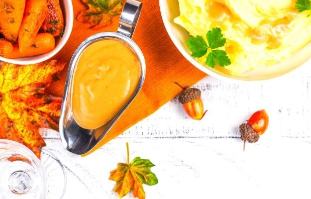vegan thanksgiving sauce in a gravy boat with maple leaves, chestnuts,, carrots and mashed potato | The Best Vegan Turkey Recipe For a Vegan Thanksgiving