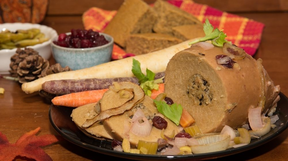 vegan turkey on black plate with lots of side dish aside | Feature | The Best Vegan Turkey Recipe For a Vegan Thanksgiving